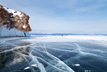 Baikal Lake in February. The car rides along the frozen Small Sea Strait near the rocks of Olkhon Island. Winter car travel on the ice of the lake. Beautiful winter landscape