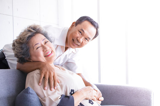 Happy senior asian couple hugging with smiling face  in living room at home