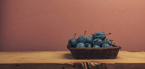 Beautiful fresh plums in basket  on a brown wooden table and red wall background.