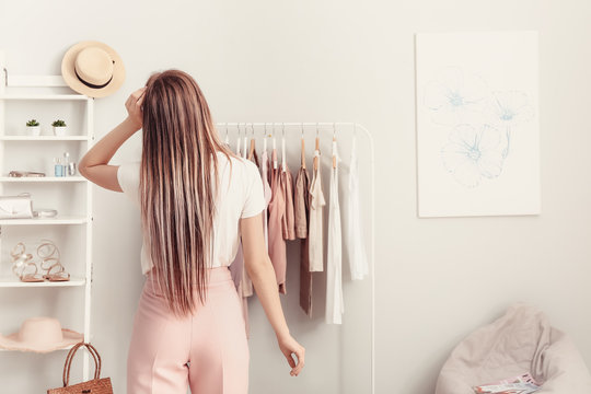 Young woman choosing clothes in her dressing room, back view