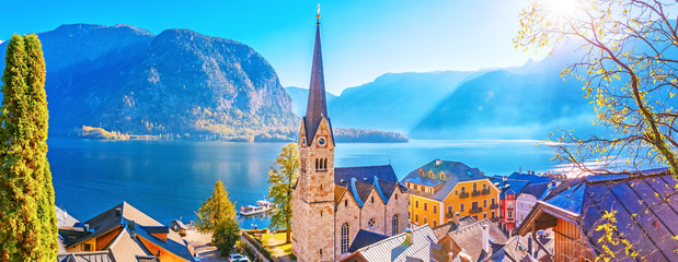 Wall Mural - Panorama of Hallstatt village and Hallstatter lake in Austria, spectacular seasonal autumn sunrise scene. View over old historical architecture and church chapel. UNESCO world heritage site, landmark.