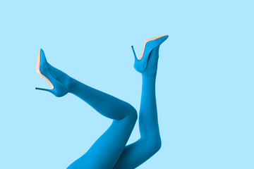 Legs of beautiful young woman in tights and high-heeled shoes on color background