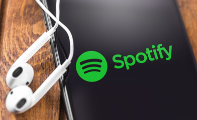 Apple Earpods and iPhone with Spotify logo on the screen. Spotify - online streaming audio service. Moscow, Russia - July 05, 2019