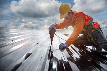 worker builder with hand drill at metal profile roof installation Metal roof construction