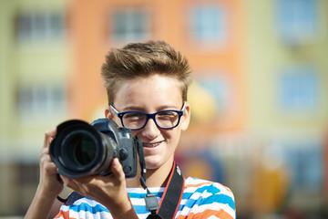 Funny teen boy with digital photo camera