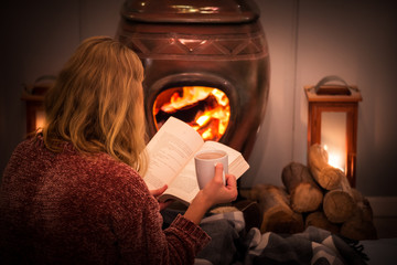 Woman/girl sitting in front of a cozy fireplace during winter under a blanket  reading a book drinking coffee/hot chocolate.