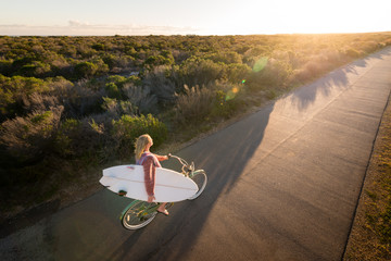 Beautiful blonde surfer girl on her way to the beach on her bicycle with her surfboard.