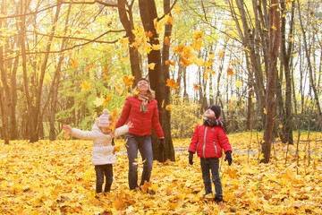 Papiers peints Attraction parc happy family walking in sunny park and throws orange maple leaves. mother with kids enjoying autumn weather outdoors