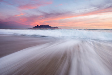 Table Mountain at sunset as seen from Blouberg with waves crashing on the beach under pink skies.