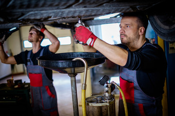 Car mechanic changes oil in a workshop