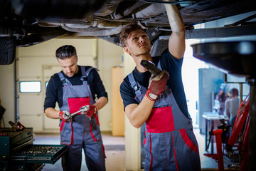 Car mechanic inspects suspension in a workshop