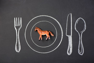 Toy horse on a plate in the figure on the chalk board
