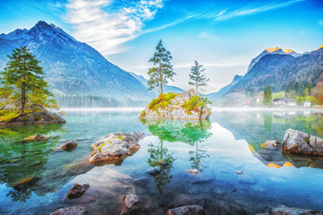 Hintersee lake in Germany, located in Ramsau parkland. Beautiful morning scenery of Alpine lake with small stone islands in the middle, growing pine tree on it. Charming Alps in Background. Europe.