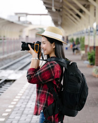 Young beautiful female travel photographer enjoys taking photo during her trip at railway station. Asian woman travel with camera having fun making pictures while waiting for train.