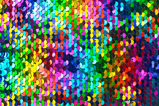 Texture of rainbow shiny sequins. Fashionable bright fabric with sequins.