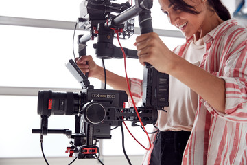 Female Videographer With Video Camera On Steady Cam Rig Filming Movie In White Studio Wall mural