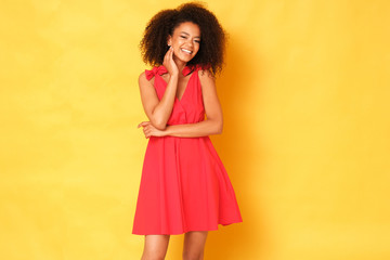 Cute afro-amercian girl in red dress on yellow background.