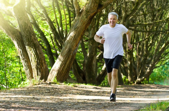 Active mature man running in summer park