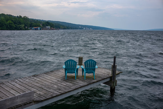 Rough waters, crash into a pier with two plastic and blue Adirondack garden chairs, as a storm comes in over Seneca Lake at Watkins Glen in New York State.
