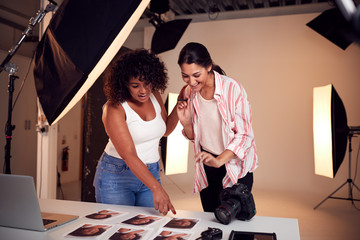 Photographer With Female Client Editing Images From Portrait Photo Shoot In Studio Wall mural