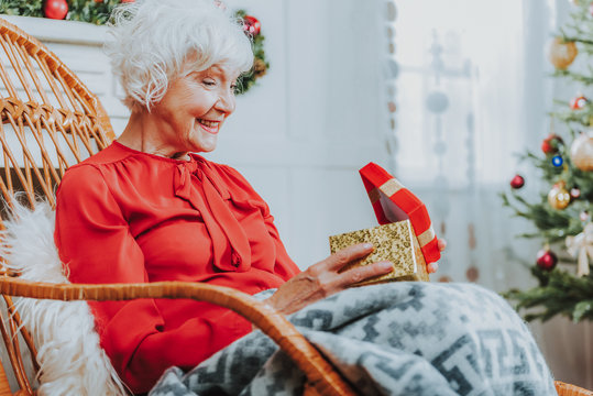Happy old woman is holding gift box
