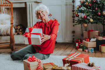 Happy old lady is holding Christmas present