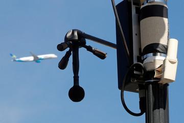 "An airplane flies past a newly installed ""noise radar"" at Villeneuve-le-Roi"