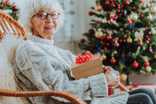 Old lady in glasses holding Christmas gift