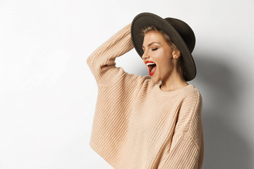 Wall Mural - Portrait of cheerful model with bright lips wearing stylish sweater and hat. Girl feeling happy posing in studio on white background. Copy space in left side. Autumn fashion concept