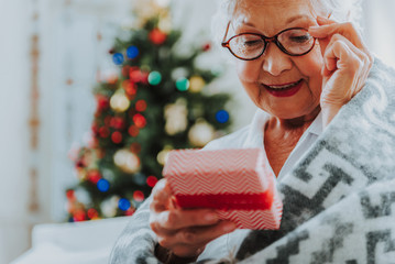 Happy old female is holding Christmas present