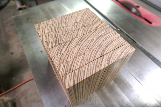 Close up of a stack of cut square blocks of exotic zebrawood sitting on edge on top of an industrial table saw in a woodworking shop for a project.