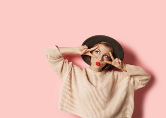 Wall Mural - Portrait of funny cheerful model wearing stylish outfit. Adorable girl in beige knitted sweater with red lips looking up with happiness. Autumn and trend concept.