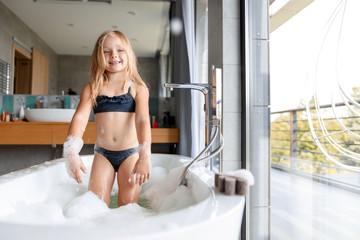 Girl in swimsuit having fun in bathroom