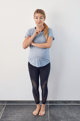 Surprised barefoot young pregnant woman standing with her hand to her chin raising her eyebrows with wide eyes standing full length against a white wall