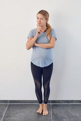 Attractive young barefoot pregnant woman standing thinking or puzzling over a problem with her hand to her chin against a white wall