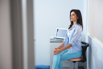 Pretty young woman sitting in dental room