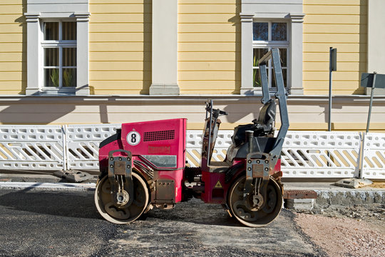 Road Construction / Germany: Small red road roller on the surface of a newly asphalted city street in the New Federal States