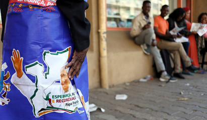 Regina Zuka wraps herself a cloth with printed image of Pope Francis she bought at a store in Maputo