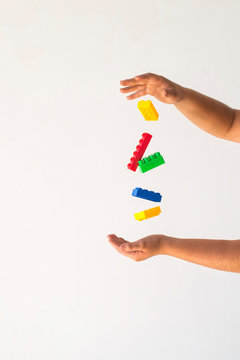 Child's hands catching multi-colored blocks of constructor.