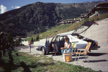 1982 vintage analog camera image of a young family driving a light blue Saab 900 during summer vacation having a picnic in the Swiss Alps.