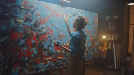 Aufkleber -  Talented Female Artist Walks to Canvas and Starts Working on a Modern Abstract Oil Painting Using Paintbrush. In the Dark Creative Studio Large Picture Stands on Easel Illuminated. Following Arc Shot