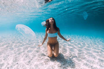 Woman underwater over sandy sea with jellyfish. Freediving in blue ocean