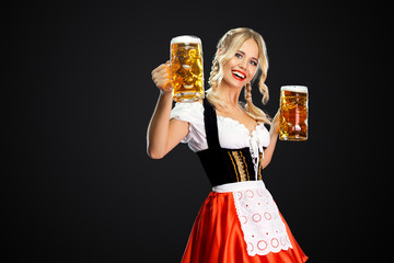 Happy sexy oktoberfest girl waitress, wearing a traditional Bavarian or german dirndl, serving two big beer mugs with drink isolated on black background.