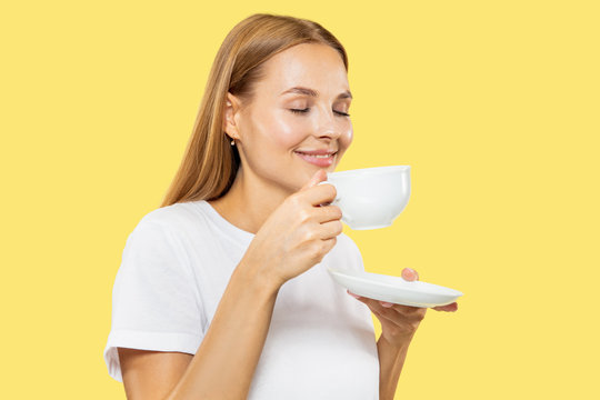 Caucasian young woman's half-length portrait on yellow studio background. Beautiful female model in white shirt. Concept of human emotions, facial expression, sales. Enjoing coffe or tea with cup.