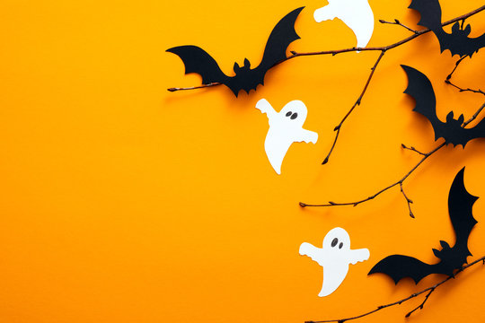 Happy halloween holiday concept. Halloween decorations, bats, ghosts on orange background. Halloween party greeting card mockup with copy space. Flat lay, top view, overhead.