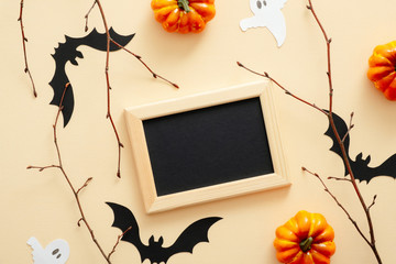 Happy Halloween concept. Halloween decorations, picture frame, pumpkins, bats, ghosts on pastel beige background. Halloween party greeting card mockup with copy space. Flat lay, top view.