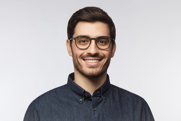 Headshot of cheerful handsome man with trendy haircut and eyeglasses isolated on gray background Wall mural