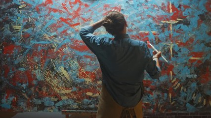 Fototapete - Talented Female Artist Energetically Using Paint Brush She Creates Modern Masterpiece of the Oil Painting. Dark Creative Studio where Large Canvas Stands on Easel Illuminated. Back View Following Shot