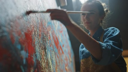 Fototapete - Female Artist Works on Abstract Oil Painting, Moving Paint Brush Energetically She Creates Modern Masterpiece. Dark Creative Studio where Large Canvas Stands on Easel Illuminated. Low Angle Close-up