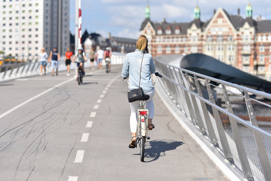 woman cyclist rides on bicycle by path of pedestrian bridge and talking phone